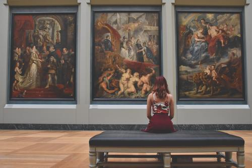 Woman Sitting on Ottoman in Front of Three Paintings