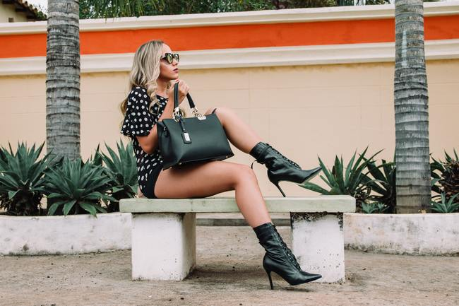 Woman Wearing Black and White Polka-dot Shirt With Black Short Shorts Holding Black Leather Tote Bag Sitting on White Concrete Bench
